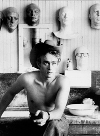 James Dean sitting with his bare upper body wearing a cowboy hat.
